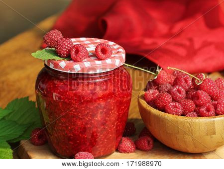 Raspberry jam and fresh raspberry on a rustic wooden table
