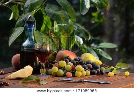 Тhe wine in the decanter and Champagne glasses with fruit on a wooden table