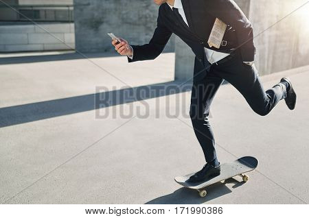 Businessman On A Skateboard Checking His Phone