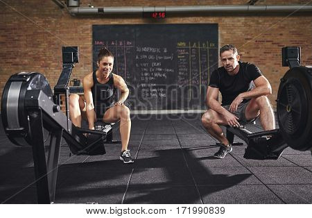Two Confident Sportsmen Sitting On Rowing Machines