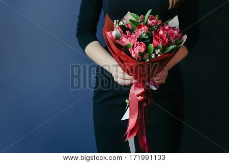 Bouquet of red tulips in girs hands. Studio, unrecognisable