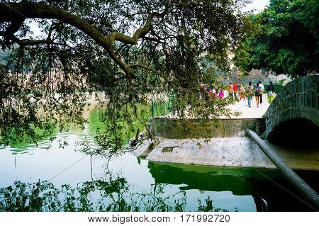Bridge crossing over a canal with trees covering the canal. People roaming around are enjoying this oasis of nature in Delhi