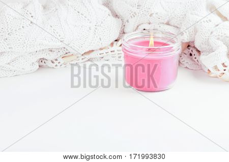 a warm knitted lace blanket and pink candle with copy Space and white background
