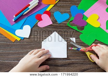 Child Cuts The Paper Items. Greeting Card With Paper Rainbow Heart. Sheets Of Paper, Glue And Scisso