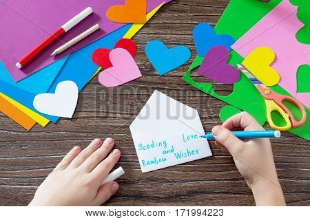 The Child Makes The Inscription Paper Items. Greeting Card With Paper Rainbow Heart. Sheets Of Paper