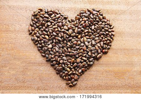 Pine nuts - small seeds of Siberian cedar pine, laid out in the shape of a heart on a wooden board.
