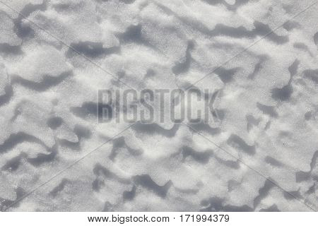 Snow texture shaped by wind and weather. Natural background.