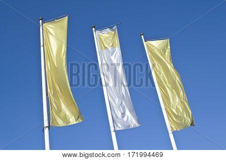 Three empty vertical banner golden flags over blue sky