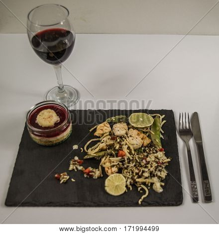 thai chicken with basmati rice coconut sauce on black stone plate with cutlerystrawberry dessert and red wine in a wineglass oriental food