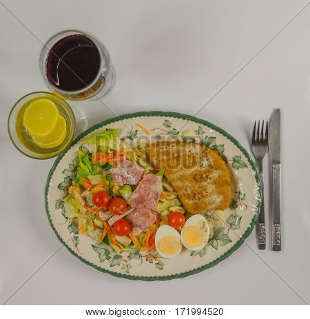 top view on a set with chicken bacon cherry tomatoes egg iceberg lettuce and a sauce of red wine in a glasswater with lemon on a decorative plate tasty lunch