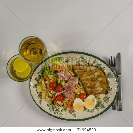 set with chicken bacon cherry tomatoes egg iceberg lettuce and a sauce of white wine in a glass water with lemon on a decorative plate a delicious lunch