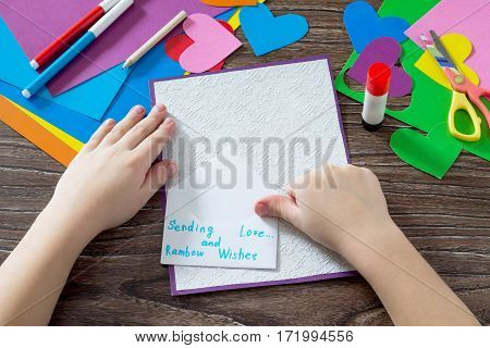Child Glues The Paper Items. Greeting Card With Paper Rainbow Heart. Sheets Of Paper, Glue And Sciss