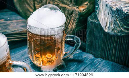 Foamy mugs of beer or ale on rustic wood