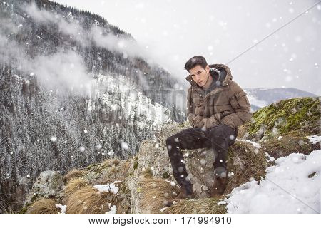 Handsome young man in winter outerwear sitting under snow up the mountain, while looking at camera