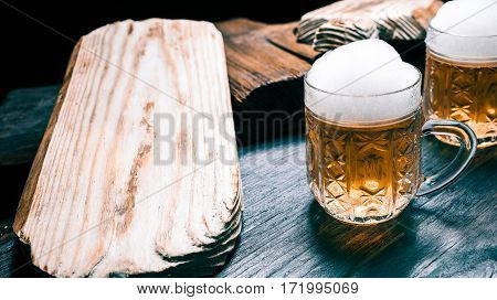Light beer or ale mugs on rustic dark wood. Closeup wide view