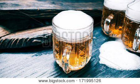 Beer or ale and overflowed foam on rustic wood bar. Closeup wide view