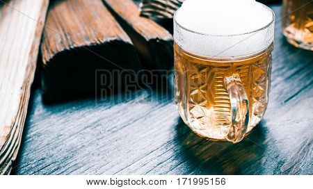 Light beer or ale on bkack counter amid rustic wood serving boards. Closeup wide view