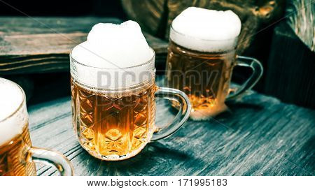 Mugs of light beer or ale on rustic wood. Closeup wide view