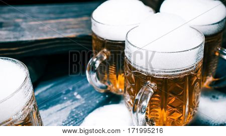 Group of mugs of beer or ale on rustic bar counter. Closeup wide view