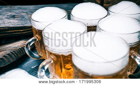 Triangled mugs of amber beer or ale on rustic wood. Closeup wide view
