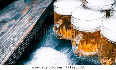 Mugs of beer or ale in line on rustic wood. Closeup wide view