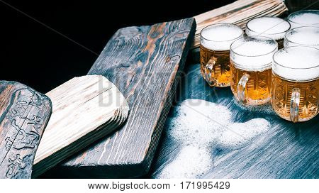 Serving boards and mugs of beer or ale on rustic wood. Closeup wide view