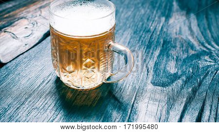 Glass mug of beer or ale on black rustic wood. Closeup wide view