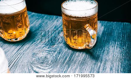 Line of mugs of light beer or ale on the edge of rustic bar counter. Closeup wide view