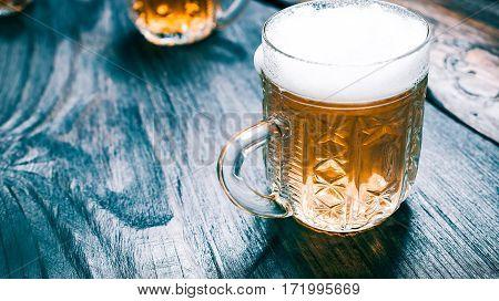Light beer or ale mugs of on black rustic wood. Closeup wide view