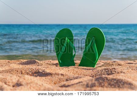 Green Flip Flops In The Sand Near The Sea