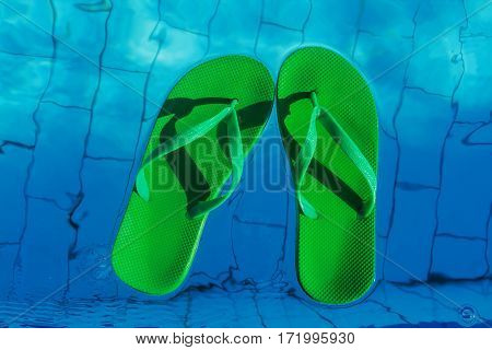 Green Flip Flops Floating In The Swimming Pool, Top View