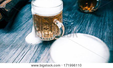 Glass mugs of overflowed beer or ale on rustic black wood. Closeup wide view