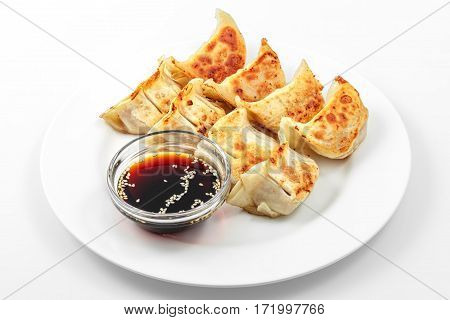 Ebi gedza hot dish, soy sauce, Japanese fried dumplings in a white plate on a white background
