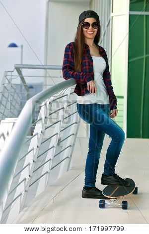 Trendy Female In Sunglasses With Skate