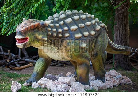 Ankylosaurus giant reptile dinosaur in forest on rocks