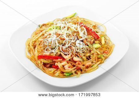 Glass noodles Singapore style, vegetables, shrimp, egg, soy sauce in a white plate on a white background