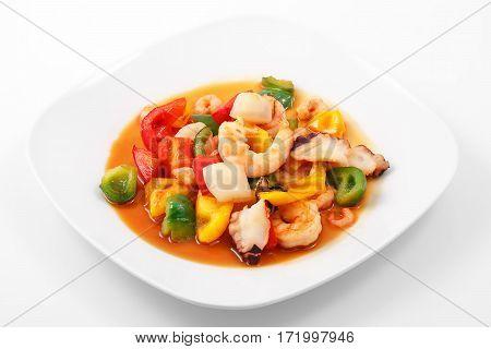 Shrimp, fried vegetables, teriyaki sauce in a white plate on a white background