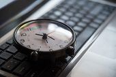 Black clock lay on keyboard time metaphor concept in dark low key tone selective focus. poster