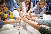 education, children, technology, science and people concept - group of happy kids building robots at robotics lesson and making fist bump poster