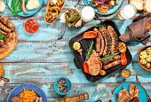 Frame of different food cooked on the grill on the blue wooden table on a sunny day grilled steak grilled sausage grilled vegetables and lager beer. Top view. Outdoors Food Concept poster