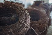 """The rusty hank of an old barbed wire lying in military warehouses waiting for """"hour of triumph"""" for use to destination - close up. The background is dissolved in bokeh and unsharpness. poster"""