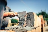 Bricklayer construction worker installing brick masonry on exterior wall with trowel putty knife poster