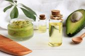 Home spa. Avocado oil facial mask, oil in bottle, white and green towels. Natural skincare treatment. poster