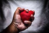 angry man crushing red heart in hand. unrequited love. love concept for valentines day. in dark tone. poster