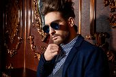 Portrait of a well-dressed imposing man in sunglasses standing in apartments with luxurious classic interior. Men's beauty, fashion. Hair styling, barbershop.  poster
