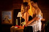 Couple dancing and kissing indoor. Romantic evening interior for loving couple. Loving people undress in intim interior. A lot of pictures in room. poster
