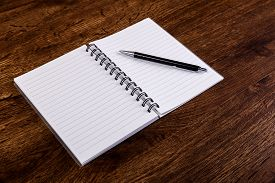 Notepad with pen on the wooden rustic desk. Mockup concept with empty notebook page. Mock-up of blank diary. Wooden rustic desk.