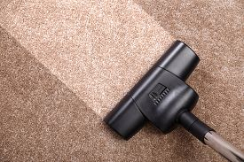 Vacuuming carpet with vacuum cleaner. Housework service. Close up of the head of a sweeper cleaning device.