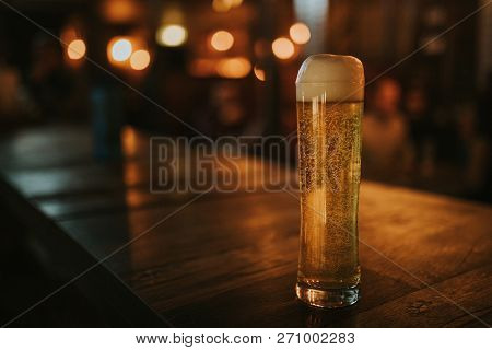 Blonde Beer Pint On A Wooden Table, With Pub Lights In The Background At Night, And Left Copyspace