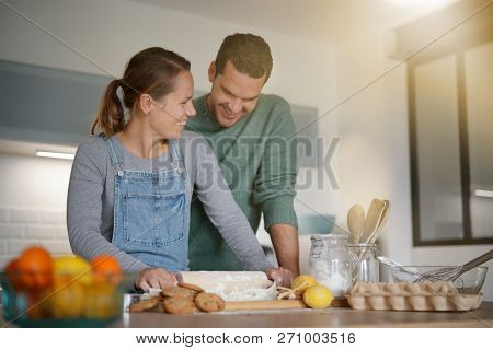 Happy young couple baking together at home